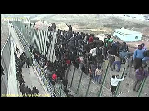 Illegal African Immigrants jumping over the border fence to get into Europe